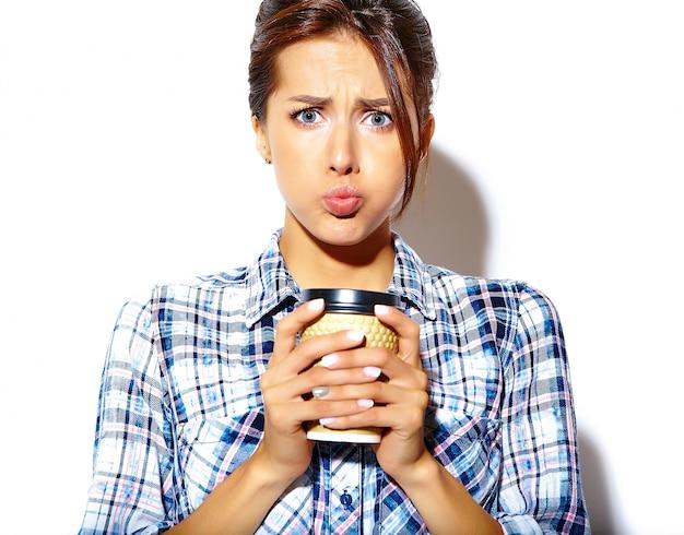 Retrato de hermosa mujer adolescente divertida y elegante con mejillas infladas en camisa a cuadros, sosteniendo una taza de café de plástico
