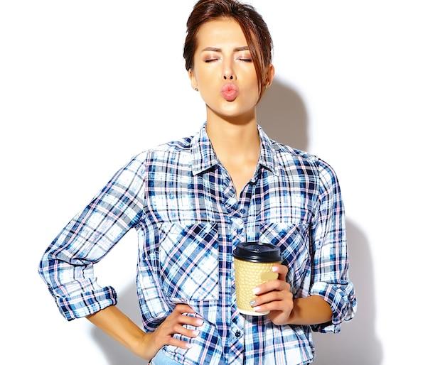 Retrato de hermosa mujer adolescente elegante con estilo en camisa a cuadros, sosteniendo una taza de café de plástico y dando un beso