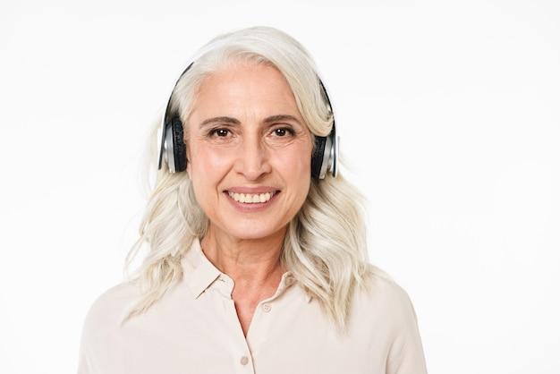 Retrato de una hermosa mujer adulta con cabello gris sonriendo con dientes perfectos y escuchando música a través de auriculares inalámbricos, aislado sobre una pared blanca