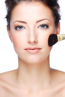 Retrato de hermosa mujer adulta joven aplicando cosméticos