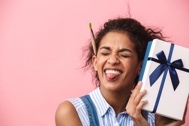 Retrato de una hermosa mujer africana joven feliz emocionado emocional posando aislado sobre la pared rosa con caja de regalo actual mostrando la lengua.