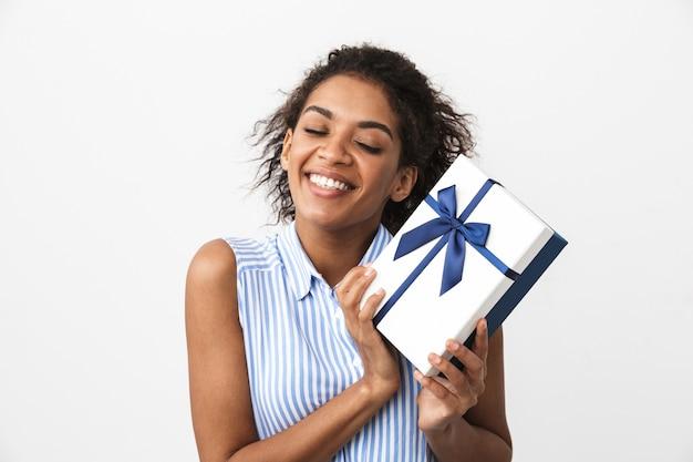 Retrato de una hermosa mujer africana joven feliz posando aislada sobre pared blanca con caja de regalo actual.