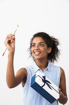 Retrato de una hermosa mujer africana joven feliz posando aislada sobre pared blanca con pincel y caja de regalo actual.