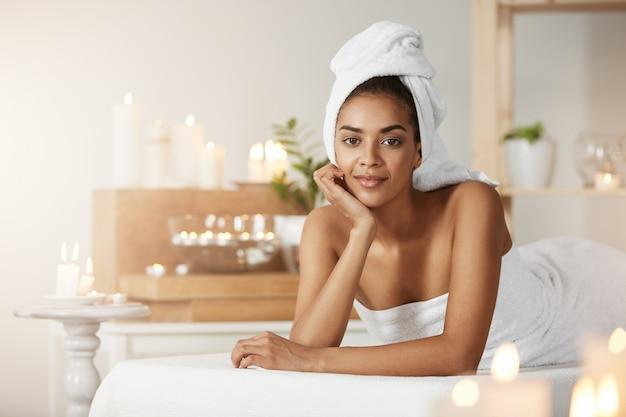 Retrato de hermosa mujer africana con una toalla en la cabeza sonriendo descansando en el salón de spa.