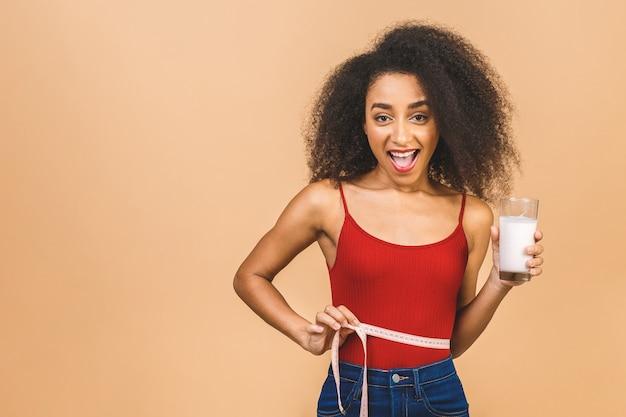 Retrato de hermosa mujer afroamericana con vaso de leche