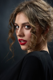 Retrato de una hermosa mujer apasionada con camisa de moda negra y lápiz labial rojo brillante