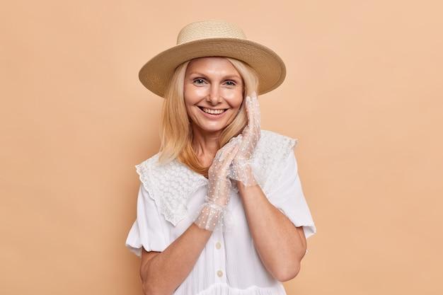 Retrato de hermosa mujer aristocrática con apariencia agradable sonríe felizmente mantiene las manos juntas viste un vestido blanco fedora y guantes de encaje expresa poses de emociones positivas contra la pared beige