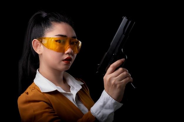 Retrato hermosa mujer asea vistiendo un traje amarillo con una mano sosteniendo una pistola en la pared negra, joven chica sexy cabello largo con una pistola mira a la cámara, mujeres bonitas está parado con una pistola