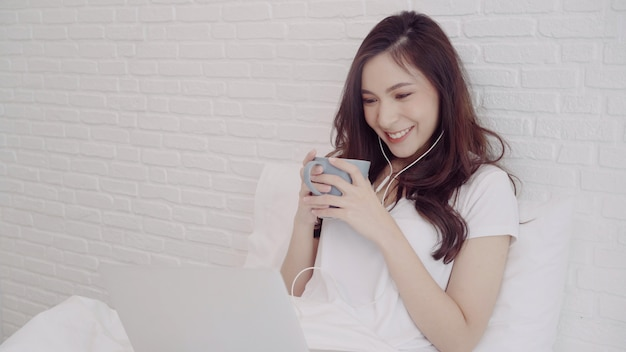 Retrato de hermosa mujer asiática atractiva usando la computadora