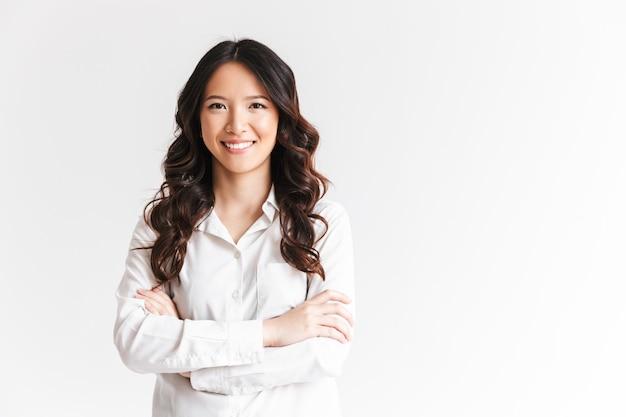 Retrato de hermosa mujer asiática con cabello largo y oscuro mirando a cámara con hermosa sonrisa y brazos cruzados