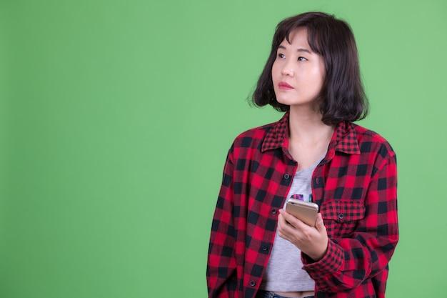 Retrato de hermosa mujer asiática hipster con pelo corto contra chroma key o pared verde