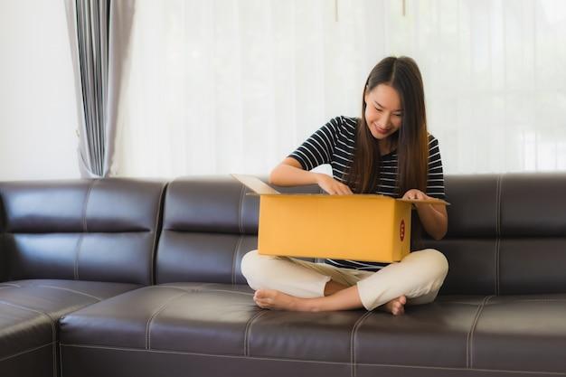 Retrato de hermosa mujer asiática joven con caja de paquete de cartón