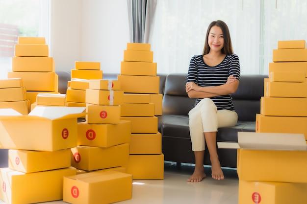 Retrato de hermosa mujer asiática joven con cajas de paquetería de cartón