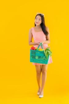 Retrato hermosa mujer asiática joven con comestibles en la cesta de compras del supermercado