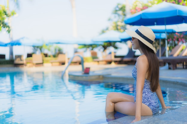Retrato hermosa mujer asiática joven feliz sonrisa relajarse piscina al aire libre en el resort