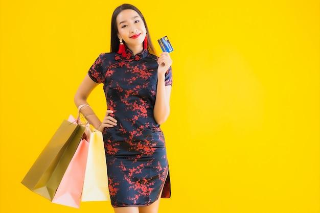 Retrato hermosa mujer asiática joven llevar vestido chino con bolsa de compras
