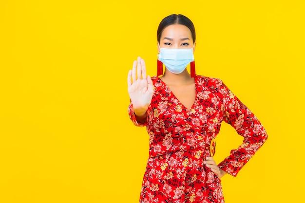 Retrato hermosa mujer asiática joven con máscara para proteger el virus corona o covid19 en la pared amarilla