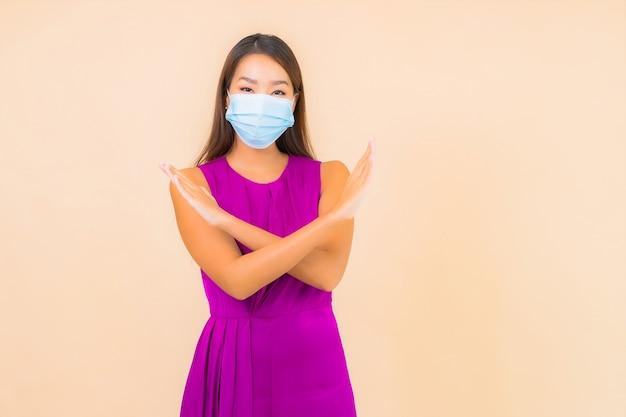 Retrato hermosa mujer asiática joven con máscara para protegerse del virus covid19 o corona sobre fondo de color