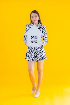 Retrato hermosa mujer asiática joven mostrar inicio o signo de la casa en amarillo