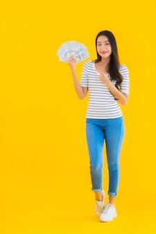 Retrato hermosa mujer asiática joven muestra mucho dinero en efectivo en dólares o dinero