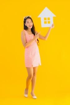 Retrato hermosa mujer asiática joven muestra signo de casa o casa