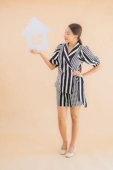 Retrato hermosa mujer asiática joven muestra signo de papel de casa o casa