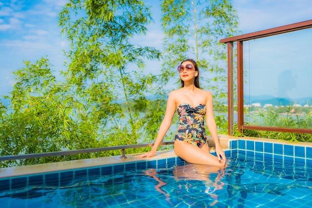 Retrato de hermosa mujer asiática joven relajante en la piscina al aire libre con vista al mar