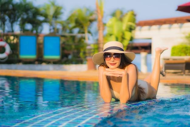 Retrato hermosa mujer asiática joven relajarse alrededor de la piscina en el hotel resort