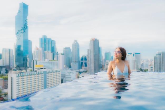 Retrato hermosa mujer asiática joven relajarse feliz sonrisa ocio alrededor de la piscina al aire libre