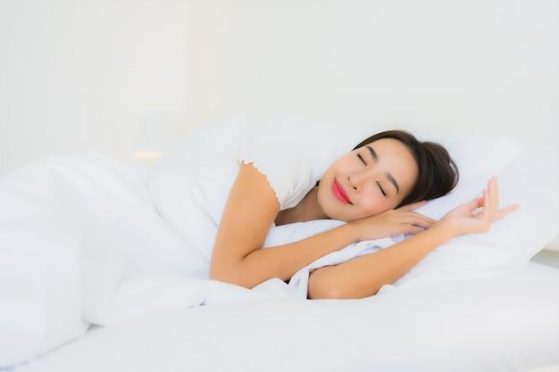 Retrato hermosa mujer asiática joven relajarse sonrisa feliz en la cama con una manta de almohada blanca