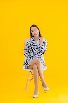Retrato hermosa mujer asiática joven sentarse en la silla con acción en amarillo