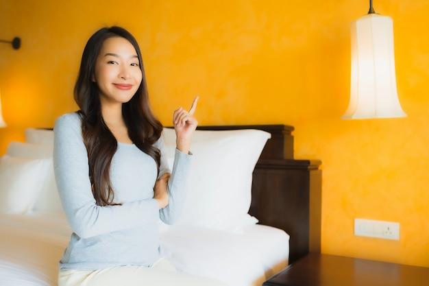 Retrato de hermosa mujer asiática joven sonriendo en la cama