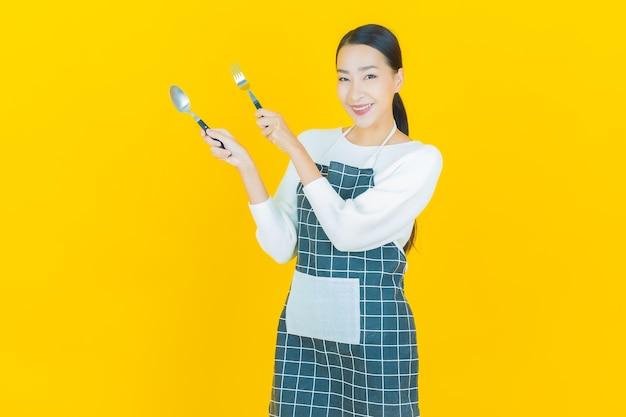 Retrato hermosa mujer asiática joven sonrisa con cuchara y tenedor en amarillo
