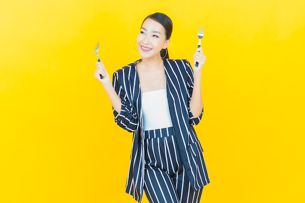 Retrato hermosa mujer asiática joven sonrisa con cuchara y tenedor sobre fondo de color