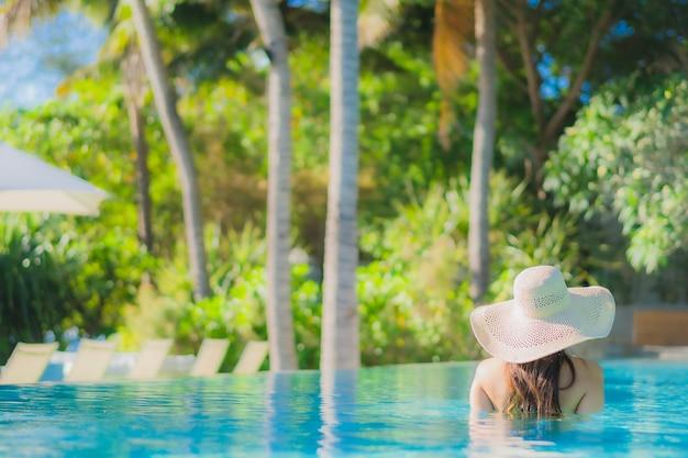 Retrato hermosa mujer asiática joven sonrisa feliz relajarse alrededor de la piscina al aire libre en el hotel resort