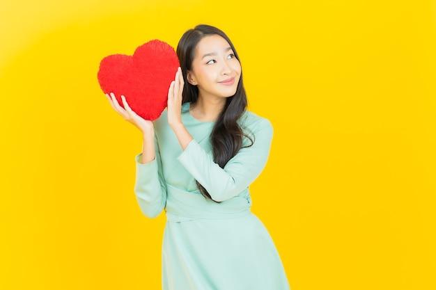 Retrato hermosa mujer asiática joven sonrisa con forma de almohada de corazón en amarillo