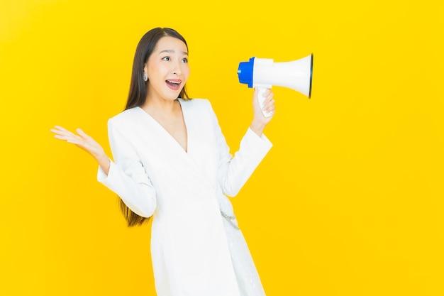 Retrato hermosa mujer asiática joven sonrisa con megáfono sobre fondo de color amarillo