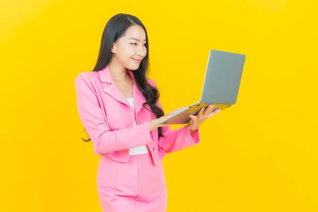 Retrato hermosa mujer asiática joven sonrisa con ordenador portátil en la pared amarilla aislada