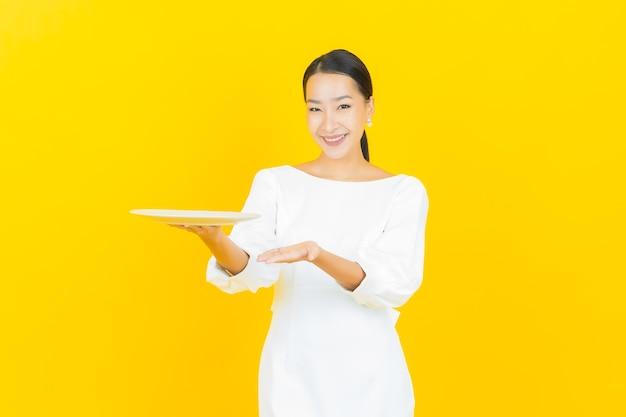 Retrato hermosa mujer asiática joven sonrisa con plato plato vacío en amarillo
