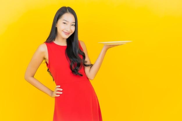 Retrato hermosa mujer asiática joven sonrisa con plato plato vacío en la pared amarilla