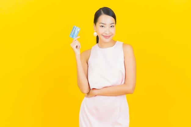Retrato hermosa mujer asiática joven sonrisa con tarjeta de crédito en amarillo