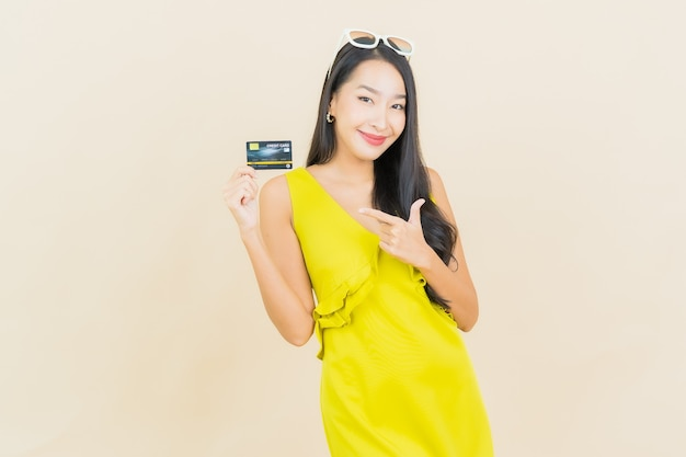 Retrato hermosa mujer asiática joven sonrisa con tarjeta de crédito en la pared de color