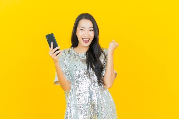 Retrato hermosa mujer asiática joven sonrisa con teléfono móvil inteligente en amarillo