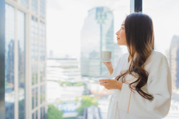 Retrato hermosa mujer asiática joven sostenga la taza de café con vistas a la ciudad