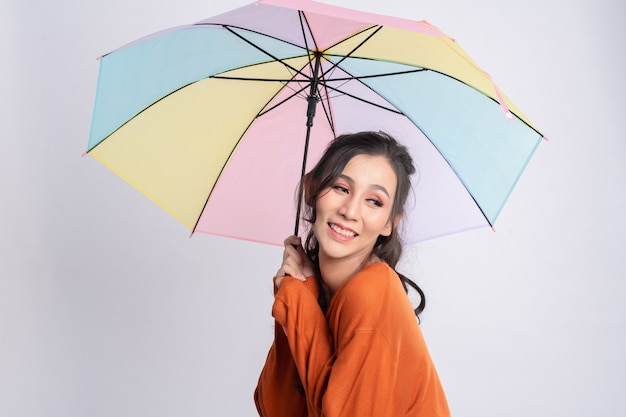 Retrato de hermosa mujer asiática joven sosteniendo paraguas, pensando en algo