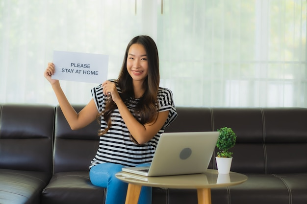 Retrato hermosa mujer asiática joven usando laptop o computadora noterbook en sofá con concepto de trabajo desde casa
