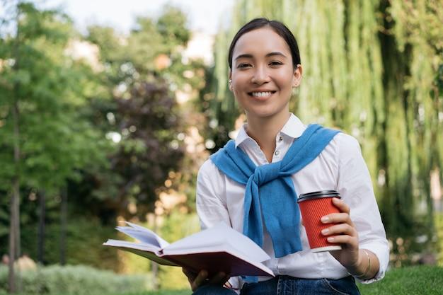 Retrato de hermosa mujer asiática leyendo el libro, tomando café al aire libre, mirando a la cámara