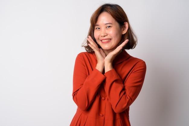 Retrato de hermosa mujer asiática con pelo corto contra la pared blanca