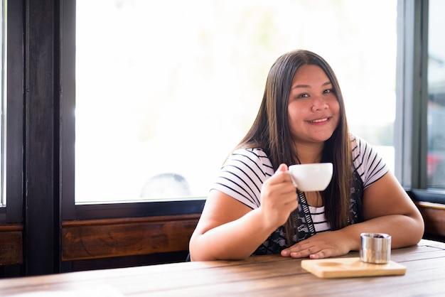 Retrato de hermosa mujer asiática con sobrepeso relajante en la cafetería.