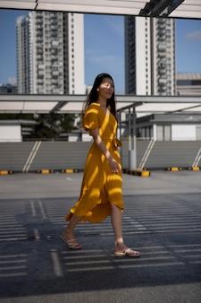 Retrato de hermosa mujer asiática en vestido amarillo posando al aire libre en la ciudad